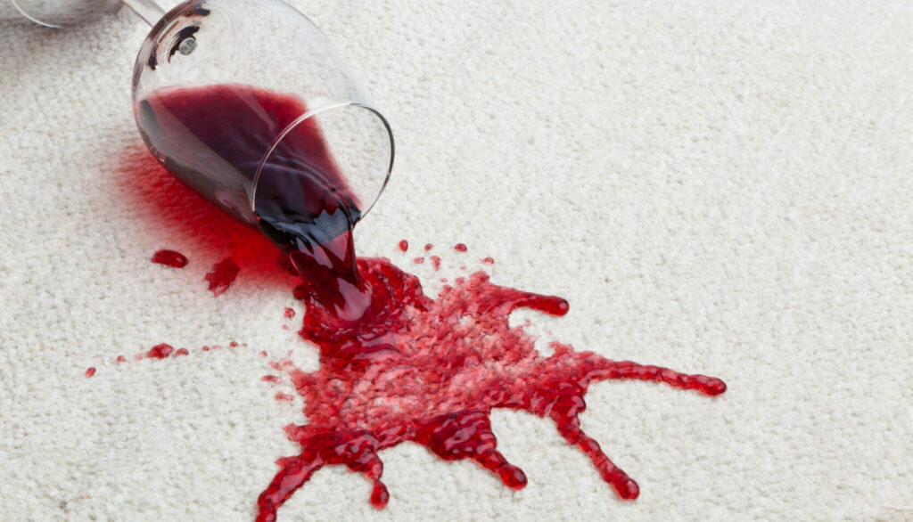 Toppled glass of red wine on carpet